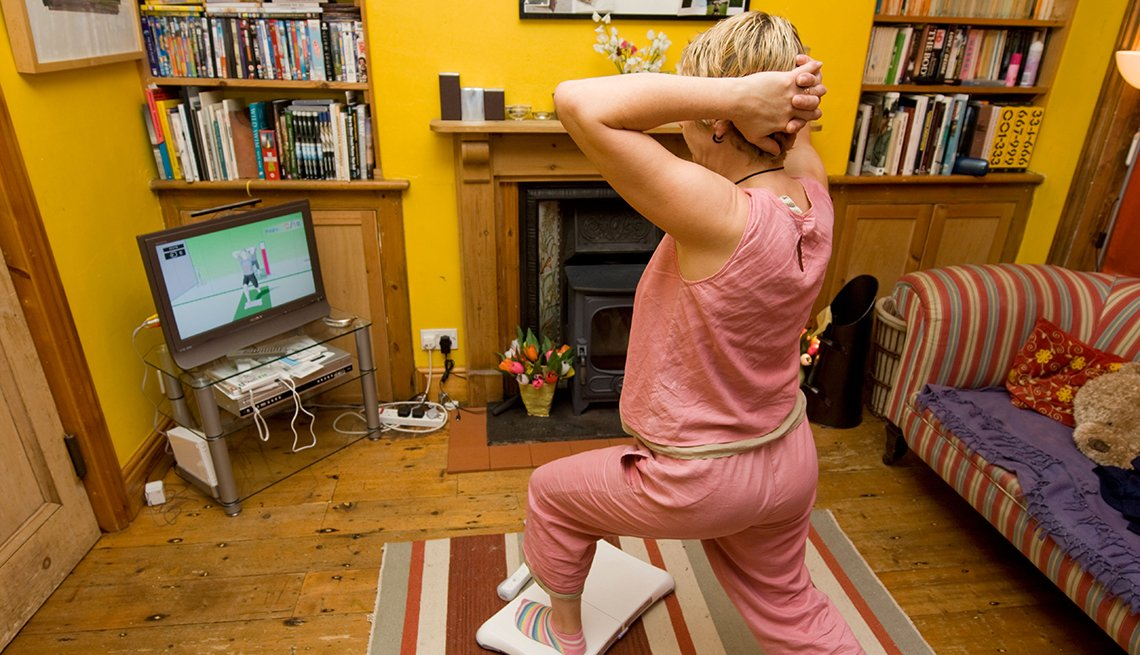 How Caregivers Can Find the Time to Exercise, Mature woman doing yoga exercises on a Nintendo Wii Fit in the living room of her house, How Caregivers Can Find Time to Exercise