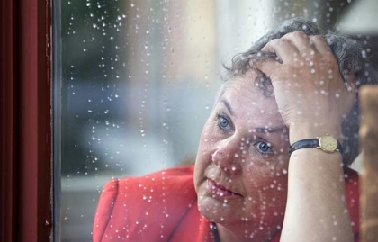 Mujer con actitud de preocupación al frente de una ventana - El matrimonio y el cuidado de los cónyuges