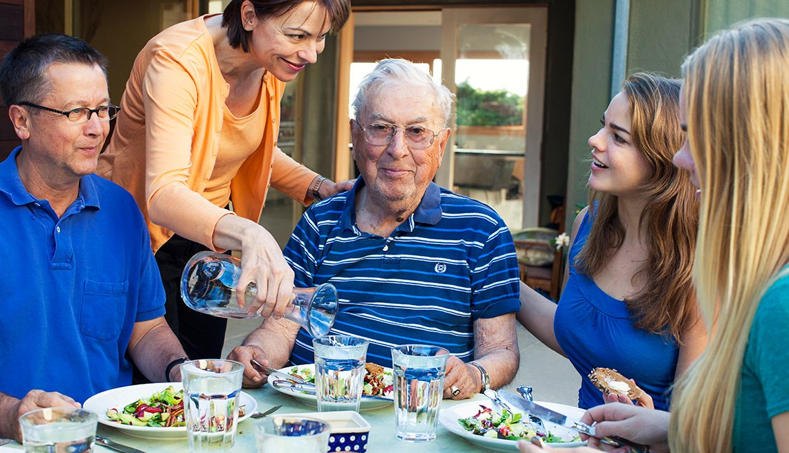 The Surprising Joys of Caregiving, Caregiver Paula Scott and her father-in-law at the dinner table along with her family