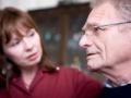 Una terapeuta habla con un hombre de edad avanzada, uso de la mentira terapéutica