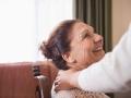 Mujer sentada sonríe a alguien que le pone una mano sobre su hombro - Estrategias para conductas difíciles de manejar