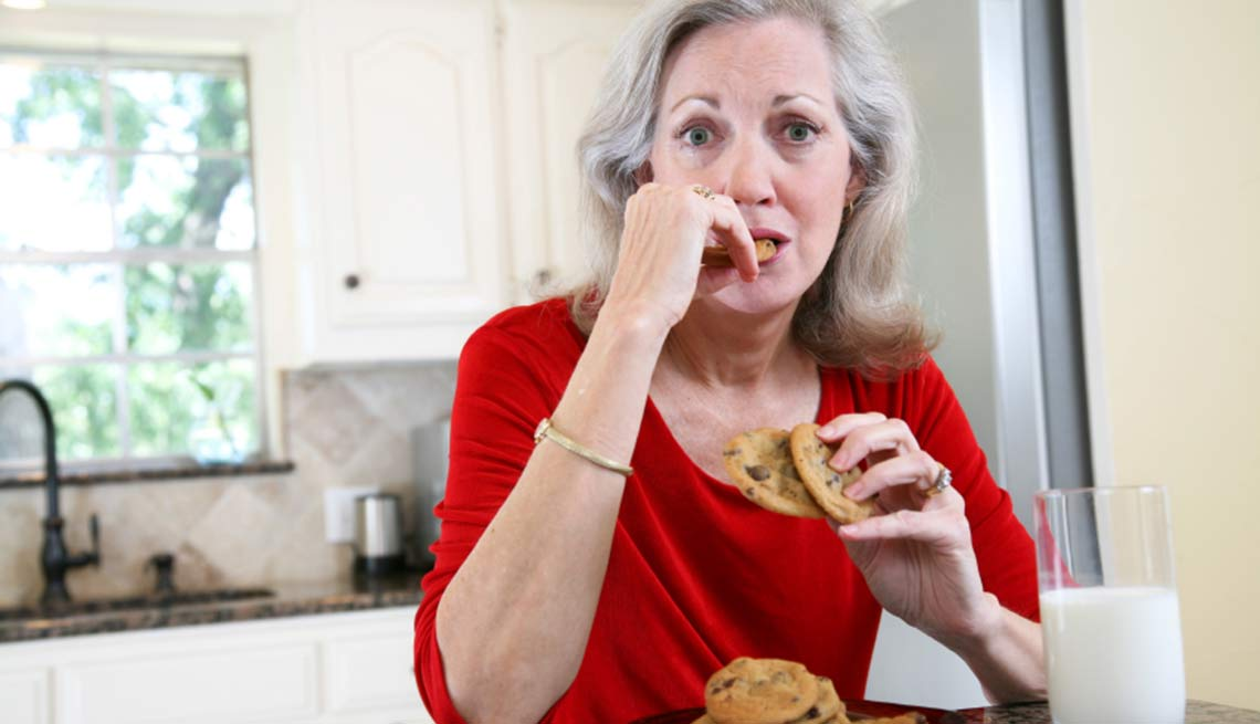 Attractive Adult Female Eating Cookies and Milk