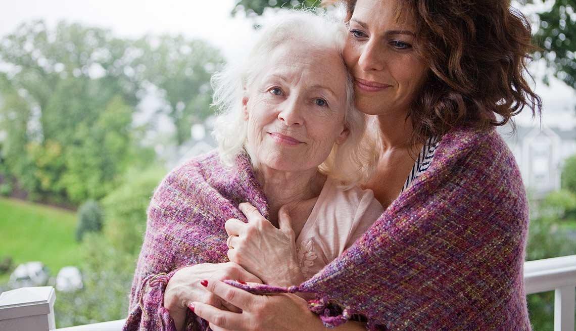 Mujer abrazando a una mujer mayor