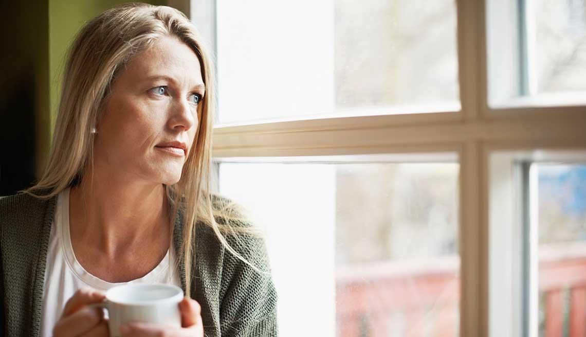 Mujer viendo por la ventana.