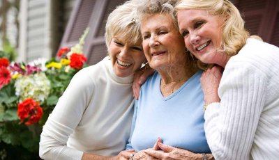 Senior woman and two daughters together on front porch, Sibling relationships and caregiving