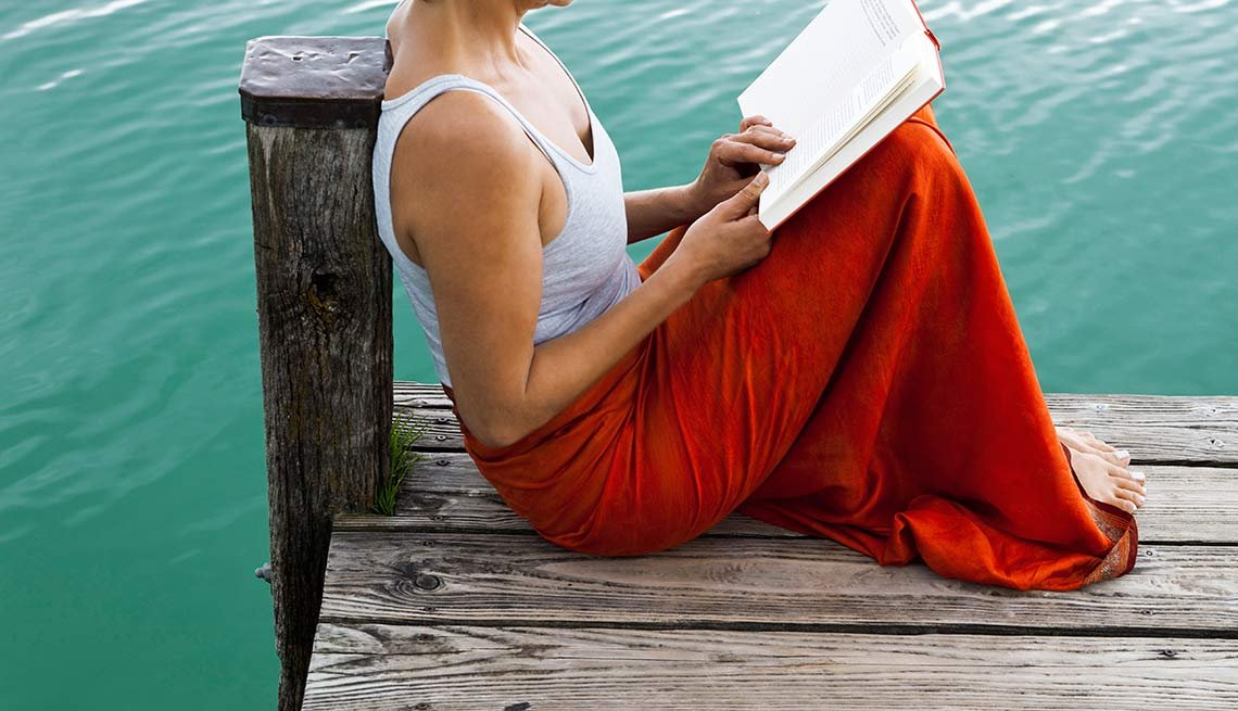 Woman reading book on a jetty at a lake, 10 Ways to Deal With Caregiver Stress