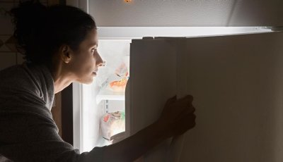 Woman looking in refrigerator in dark, How Sleeplessness Leads to Overeating