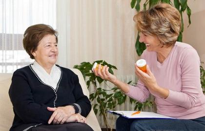 Cómo consumir los medicamentos correctamente - Mujer sostiene medicamentos en las manos mientras habla con otra mujer