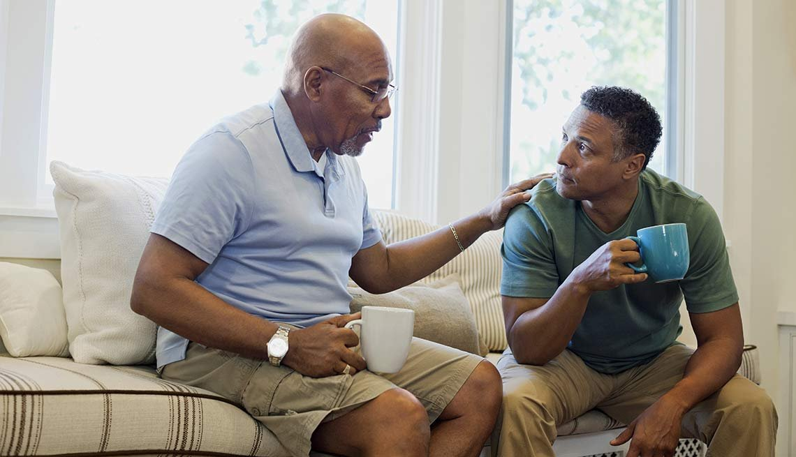 Padre e hijo conversan sentados en un sofá mientras toman un café