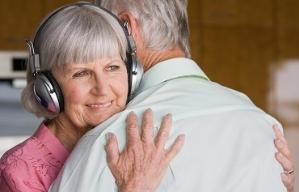 Mujer mayor con audífonos abraza a un hombre - La importancia de los aparatos auditivos en el cuidado