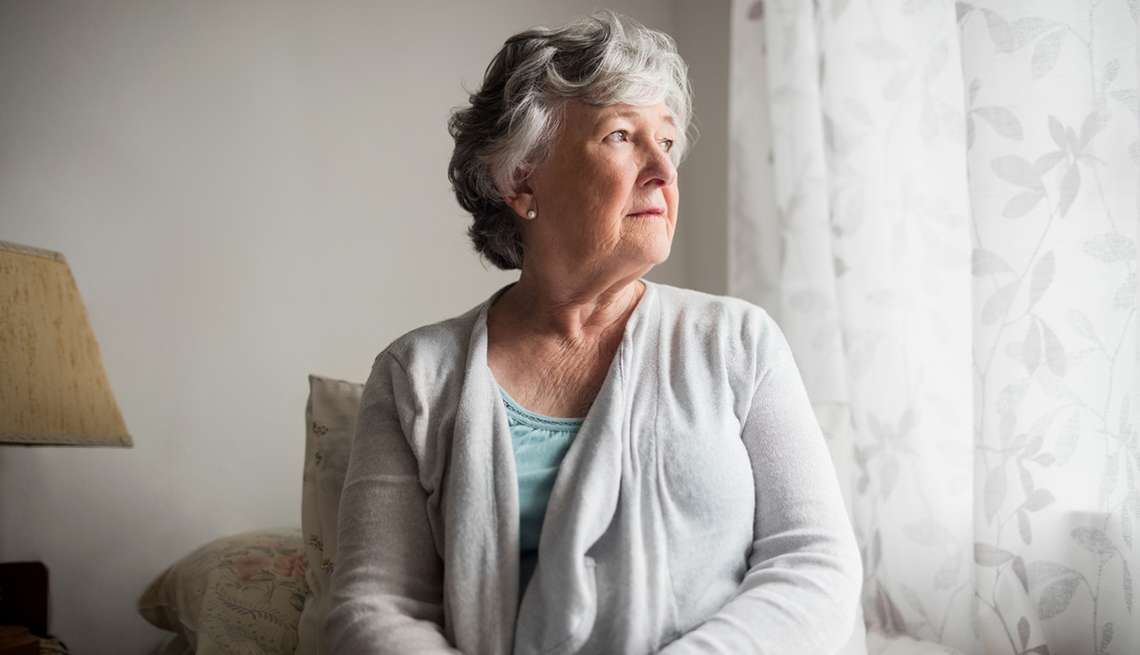 woman looking out a window: Caring for a loved one at home