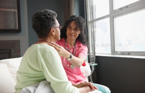 Contratar servicios de cuidados en el hogar - Enfermera atiende a mujer mayor