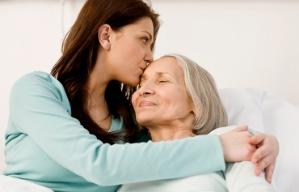 Cuidar de un ser querido es una labor costosa - Mujer joven abraza a una mujer mayor