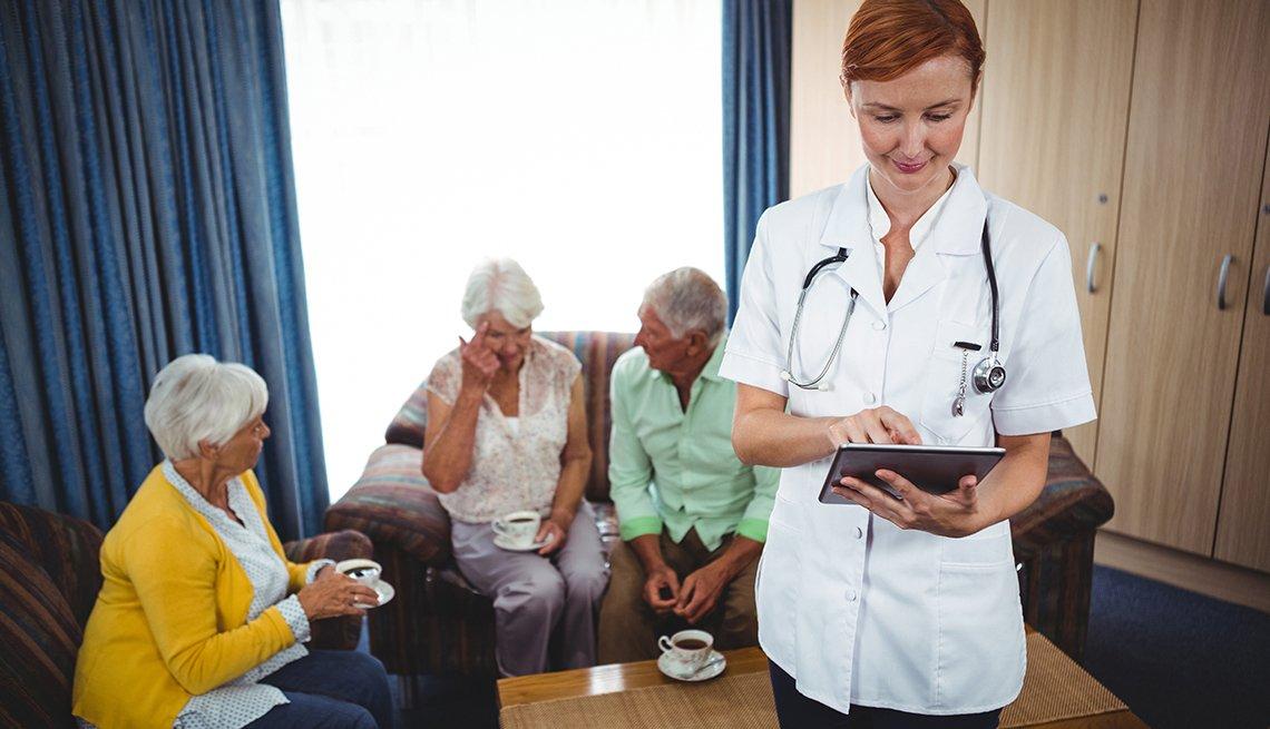 Adultos mayores en sala de espera junto a enfermera - Medicare: preguntas y respuestas
