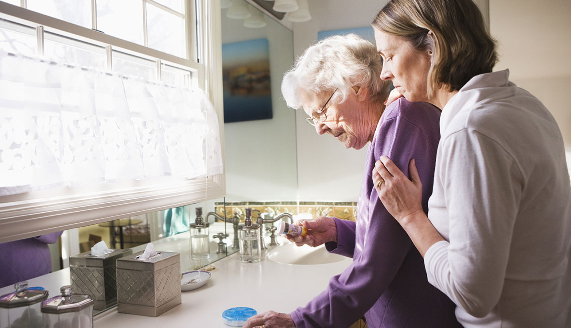 Daughter holding her senior mother in the kitchen