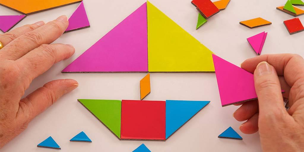 Manos construyendo un rompecabezas de diversas formas y colores