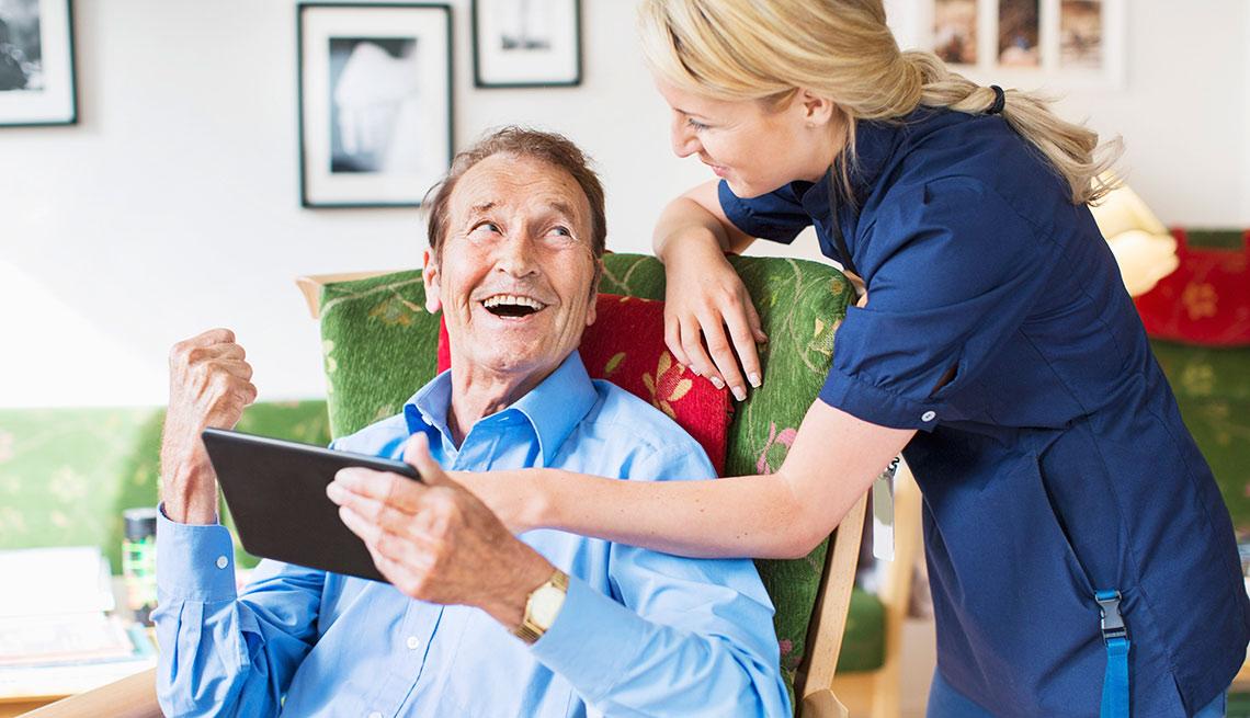 senior man smiling at his caregiver while using tablet