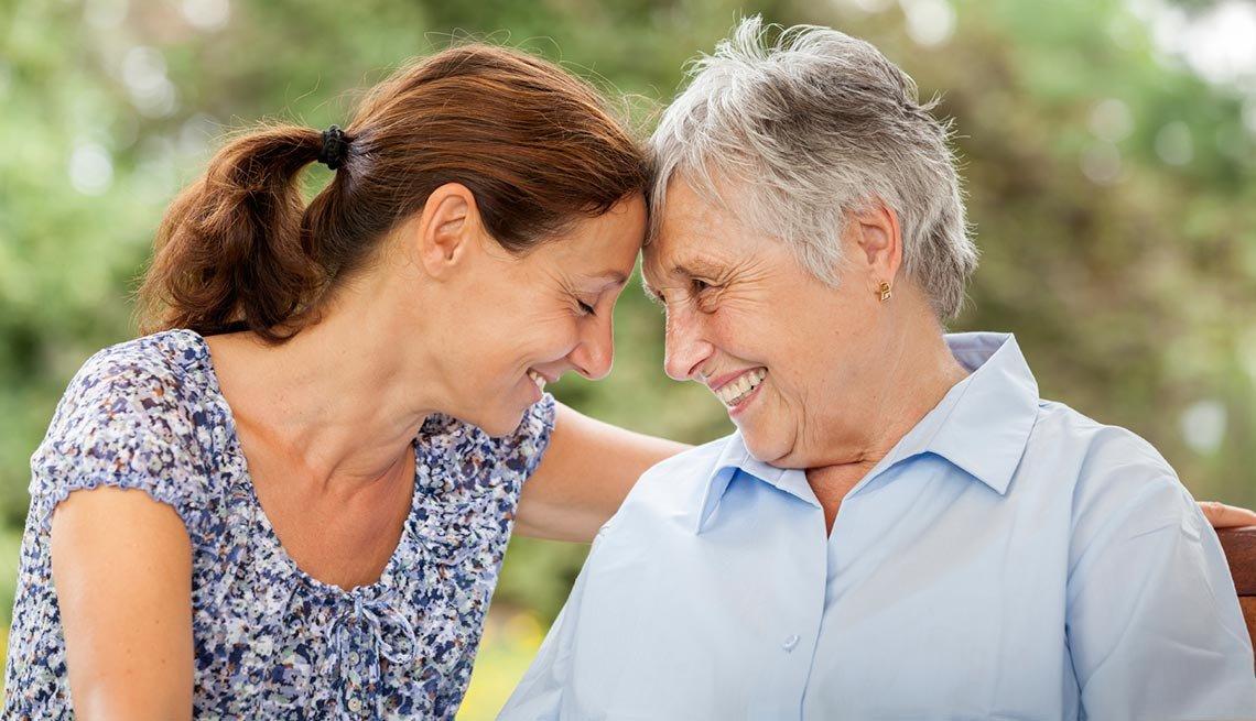 Senior woman and caregiver outdoors in a garden