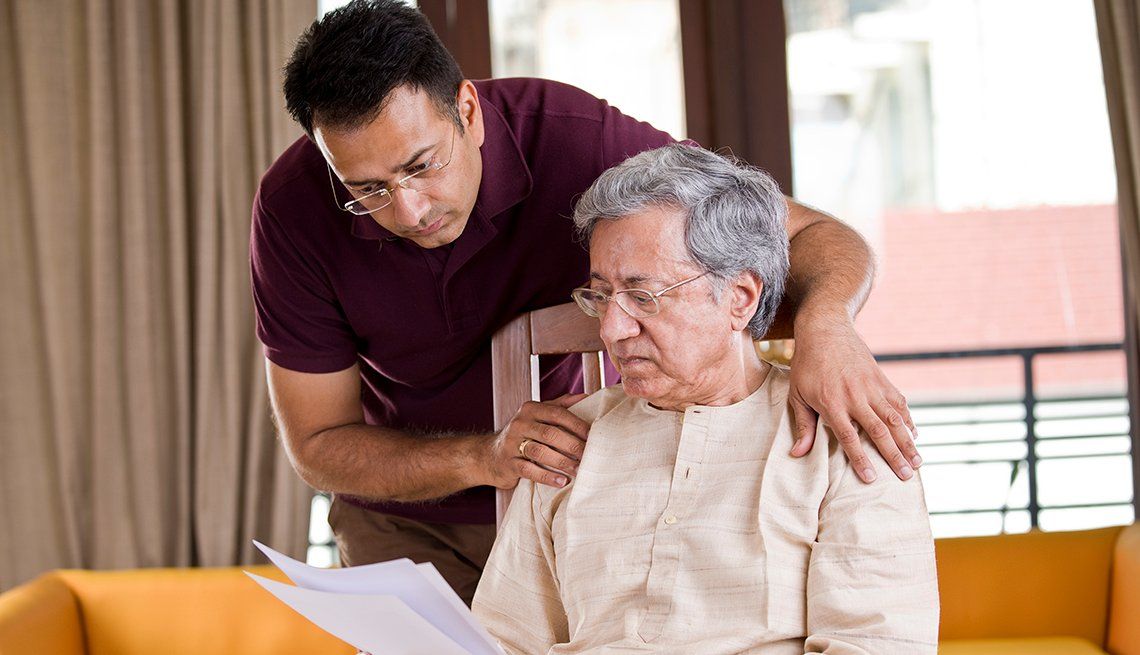 Hijo ayuda a su padre con unos documentos