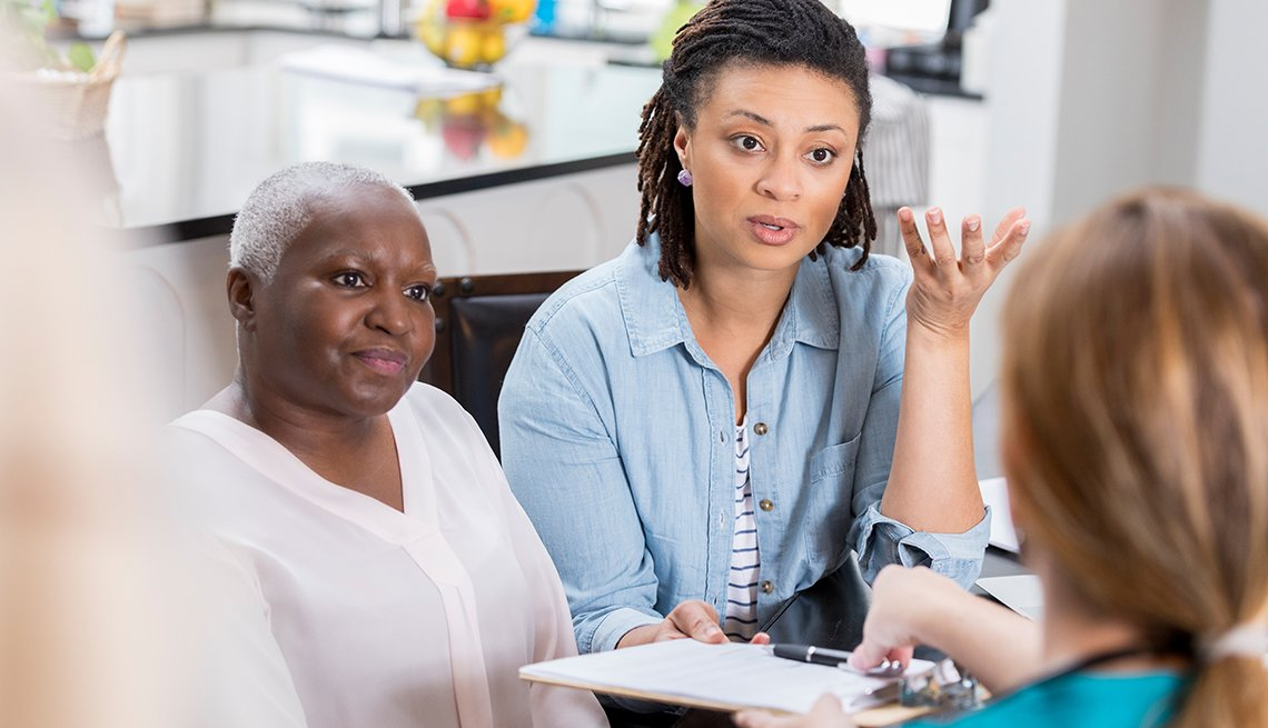 Concerned adult woman and her mother talking with a healthcare professional about her mom's health insurance