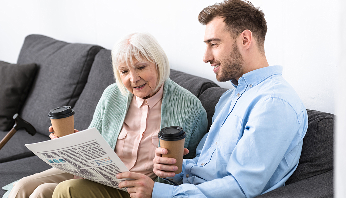 Man reading the newspaper to his mother while they sit on the couch and drink coffee