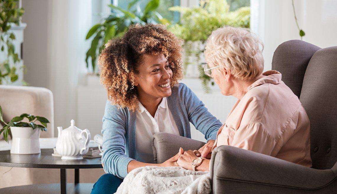 Mujer joven ayuda a una mujer mayor en un hogar