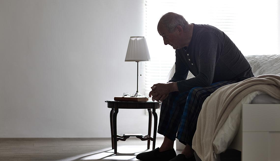 Abuelo sentado en la cama mira al suelo - Huérfanos de la tercera edad