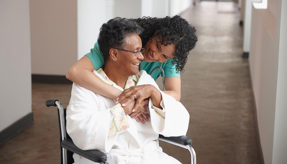 Enfermera abraza y se ríe con una mujer adulta sentada en una silla de ruedas