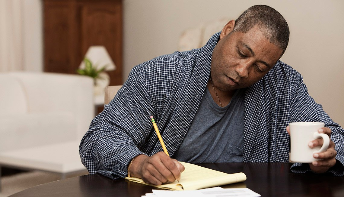 Un hombre crea una lista de cosas por hacer mientras toma café