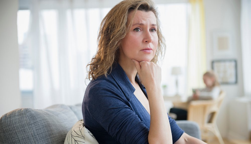 Worried Woman on Couch, Daylight White Curtains, Help for Long-Distance  Caregivers