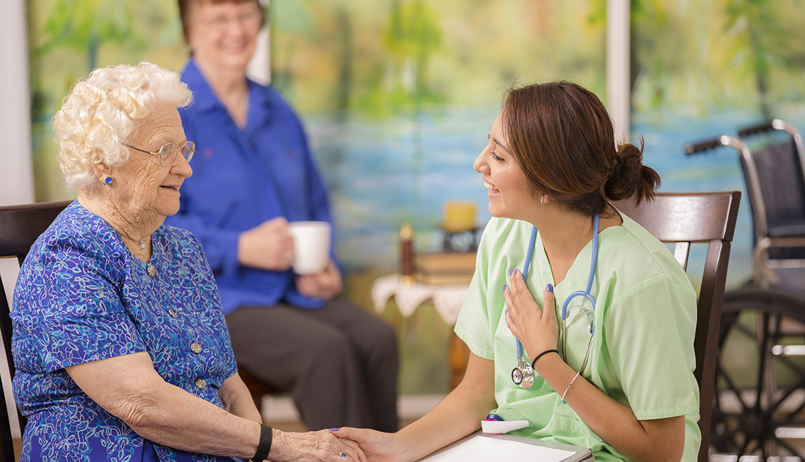 Elderly Female Caucasian Patient Talks To Nurse With Her Adult Daughter In  Background, How To