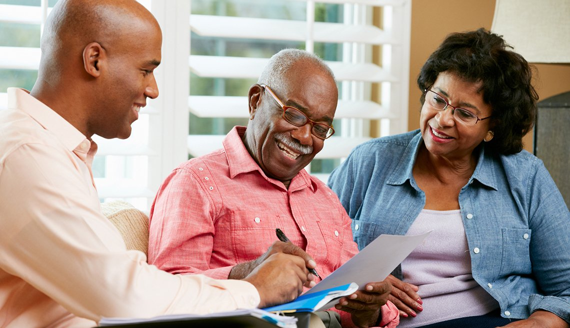 Financial Advisor Talking To Senior Couple At Home, Wills and Trusts, Caregiving, AARP,