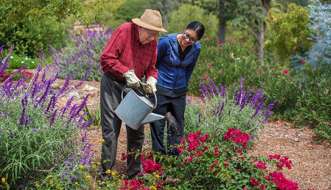 Una mujer acompaña a un hombre mayor mientras riega las plantas