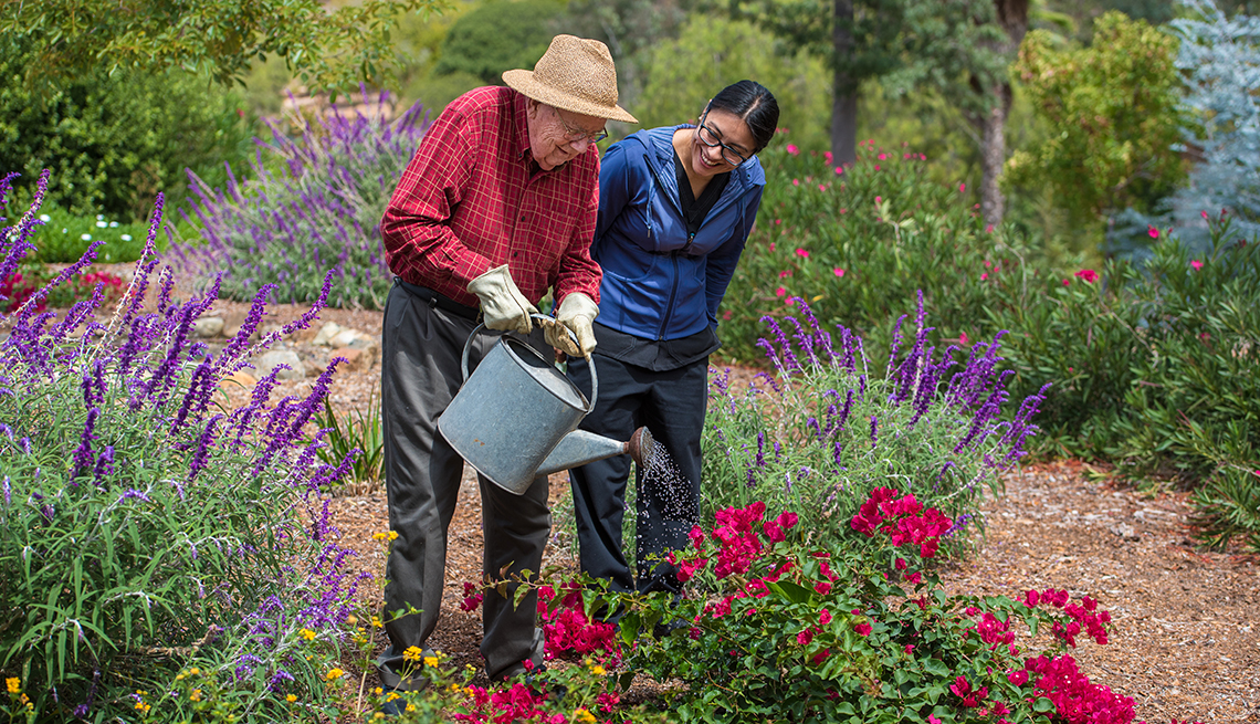 Elderly Man Flowers Watering Can, Nurse in Blue Helps, Assisted Living: Weighing the Options