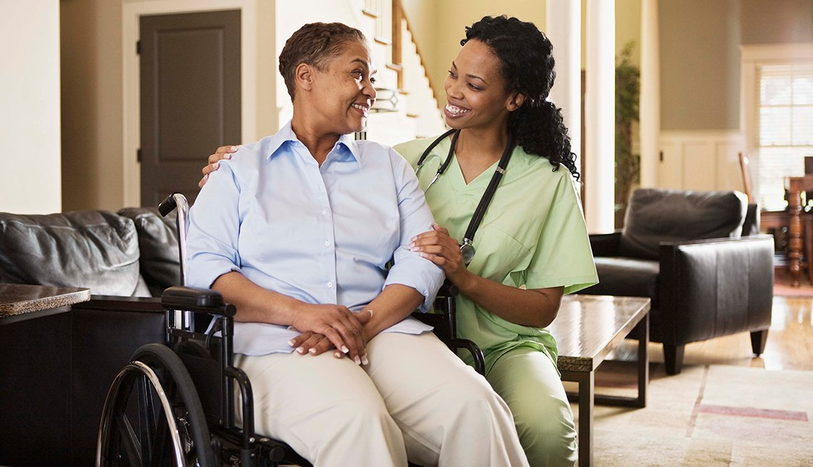 Woman in wheelchair talking with a female nurse inside a home