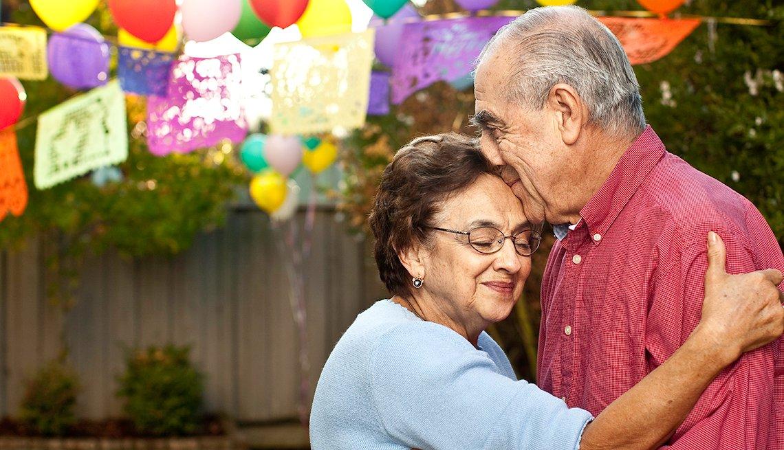 Hombre y mujer mayores, abrazados en una celebración en el patio de una casa.
