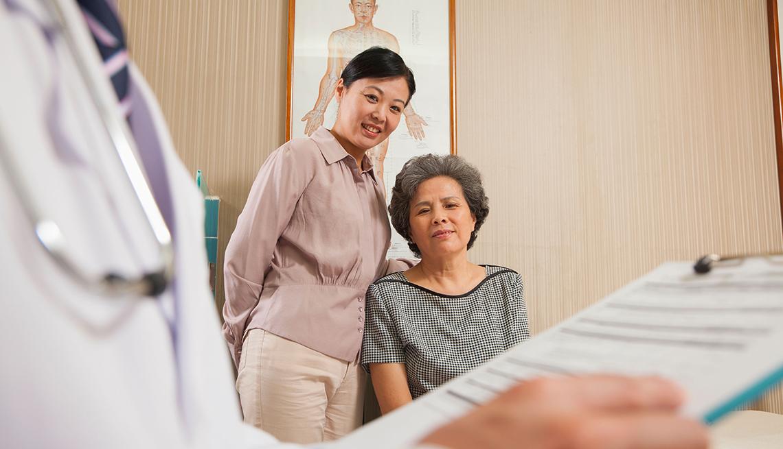 Mujer mayor sentada y mujer más joven de pie