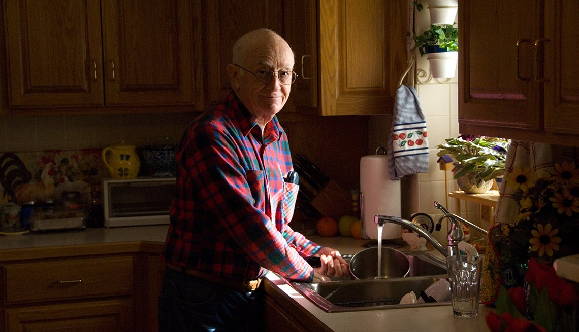 Mature man washing dishes at the sink in a kitchen