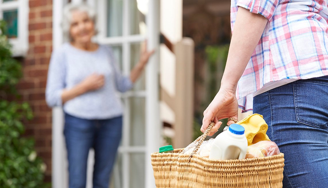 Female Volunteer Carrying Groceries To Elderly Neighbor In Background, How Community Service Can Help With Care