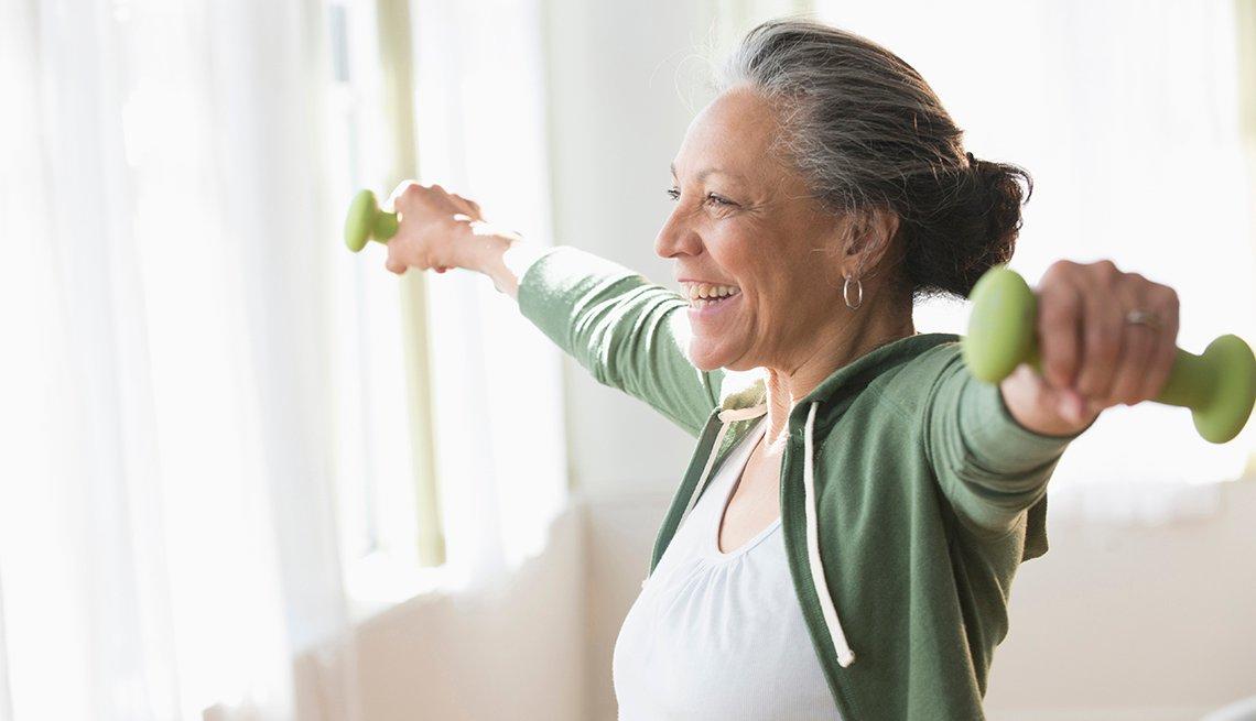 Una mujer hispana mayor levanta pesas en una sala de estar bien iluminada.