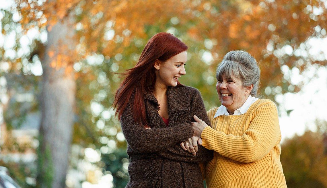 Mujer mayor sonríe mientras camina junto a una mujer joven