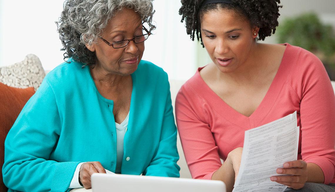 Mujer y su madre miran un documento