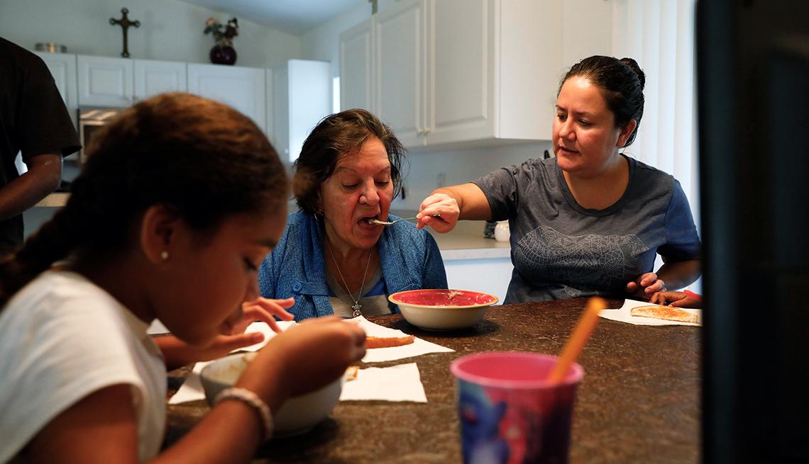 Olivia García le da de comer a su mamá