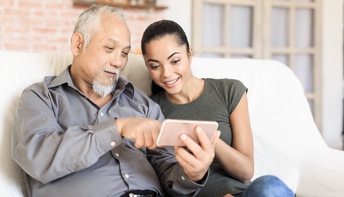 Adult daughter showing her father how to use a mobile phone
