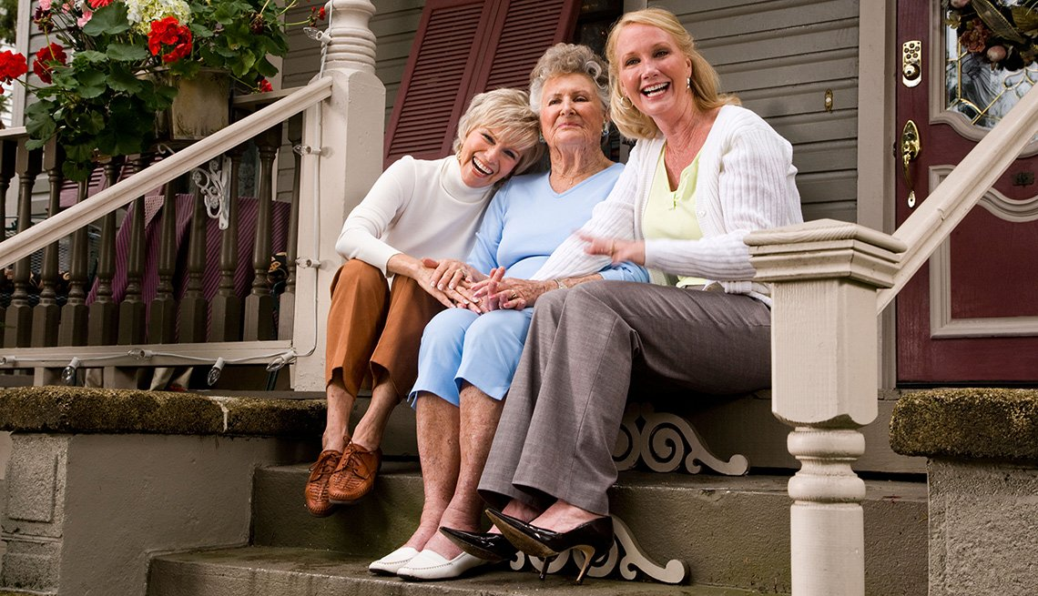 three women sitting on the stairs in front of house