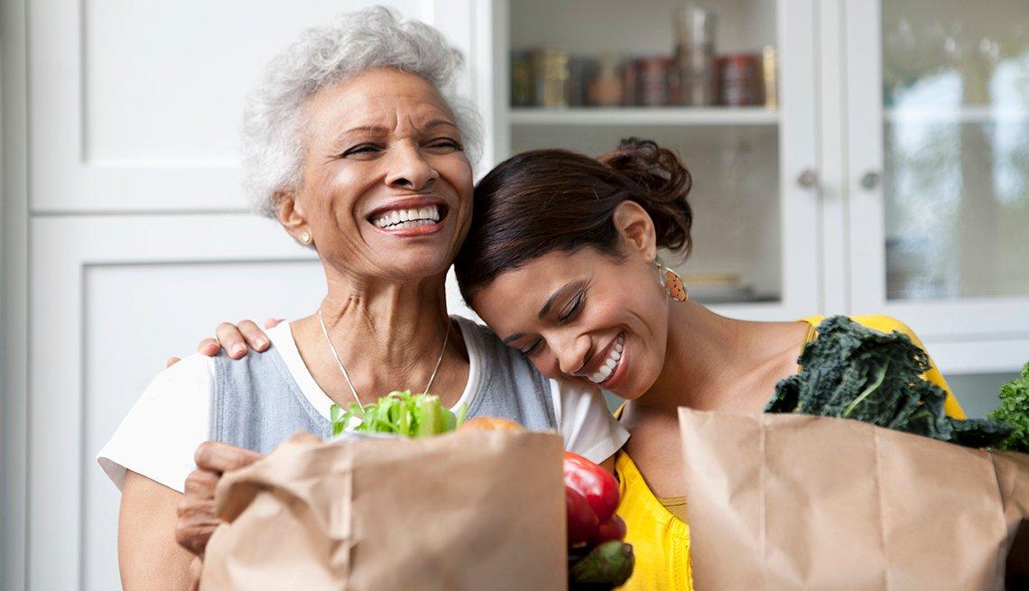 Madre e hija adulta llegan al hogar con bolsos de víveres