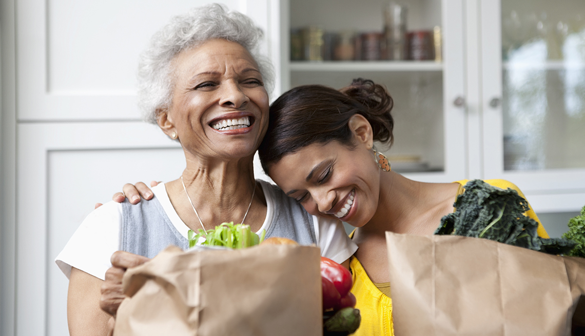 Mom and adult daughter bringing groceries into the kitchen
