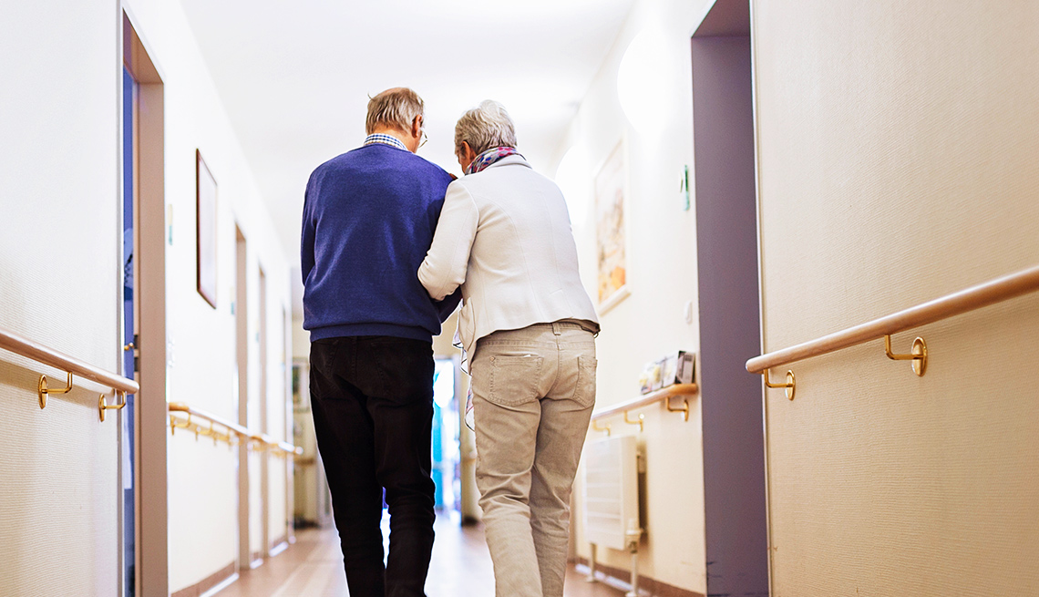Two people walk down the hallway of an assisted living facility