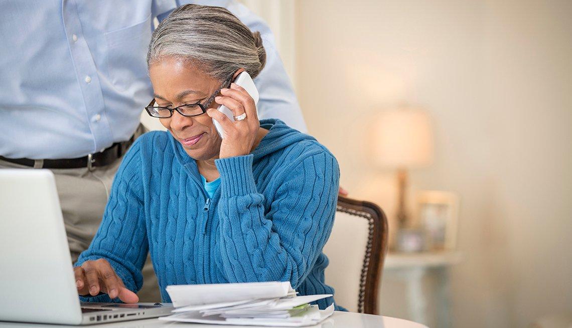 Mujer paga sus cuentas por internet, mientras está sentada frente a su computador.