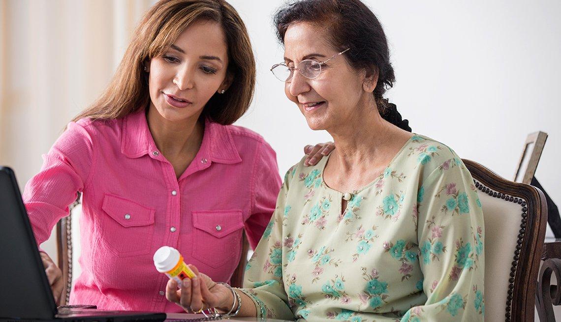 Una mujer joven asistente con su medicación a una mujer mayor.